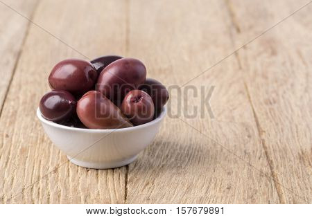 olives into in a bowl on wooden table background