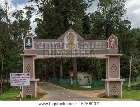 Ooty India - October 25 2013: The man rectangular gate over road into Wellington Cantonment. Features names and logos of garrison and college. Green foliage in back. Guard on duty.
