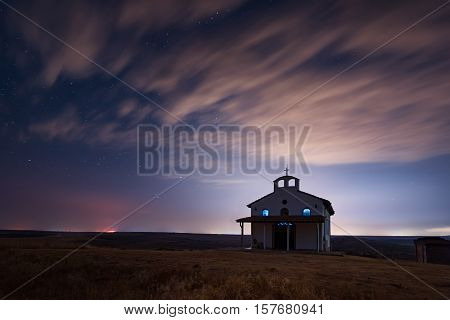 Starry cloudy night over the Chapel of St. George, Rusokastro village, Bulgaria
