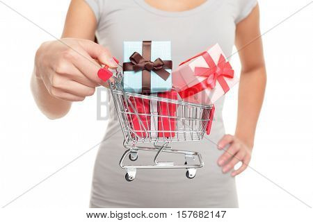Miniature shopping cart with Christmas gifts for holiday shopping on boxing day or black friday. Closeup of woman hands holding mini toy object for spending concept.