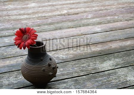 On a wooden deck sits a pottery vase.