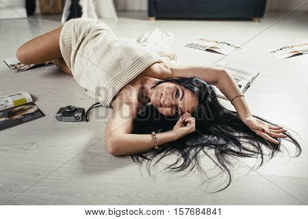 Warm toned picture of curvy sexy young brunette woman lying on floor among the glamorous magazines