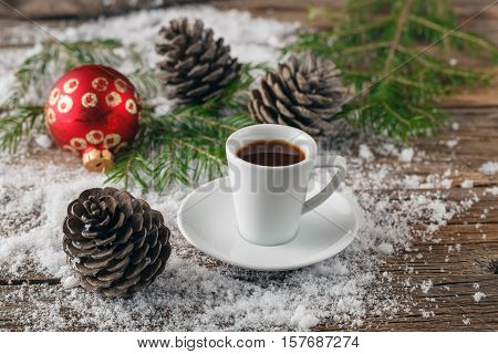 Cup of coffee and christmas toys on wooden table.