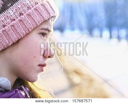 teen girl half face portrait in knitted hat on snow winter park sunny background