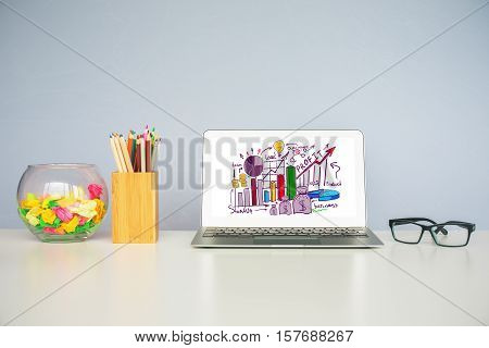 Front view of workplace with business sketch on laptop screen. Finacial report concept