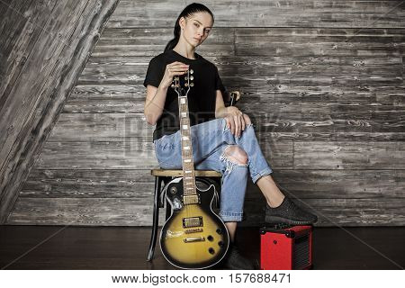 Beautiful girl with electric sunburst guitar sitting on amplifier in wooden room. Music concept
