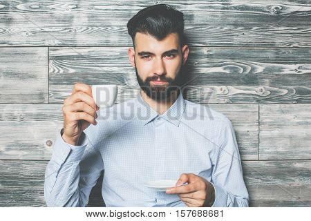 Close up portrait of handsome bearded young man with coffee cup on wooden background
