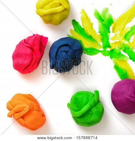 Several balls of multicolored plasticine on the white background. Art and creativity. Kid's games and activities. Handmade objects.