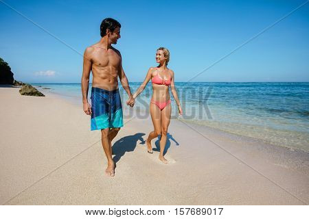 Full length shot of young couple holding hands walking on the beach. Young man and woman strolling on the sea shore.