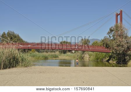 MARBELLA, SPAIN - MARCH 31, 2015: Boy fishing at the mouth of the river and people passing by the wooden bridge in green river beach in Marbella Andalusia Spain