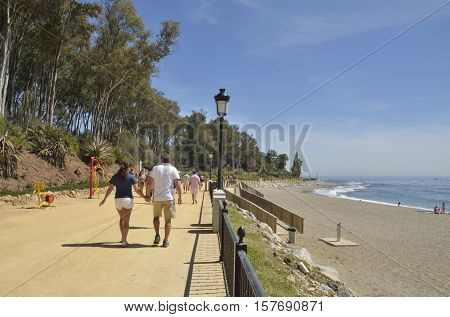 MARBELLA, SPAIN - MARCH 30, 2015: People walking by the promenade beach along the Mediterranean sea in Marbella Andalusia Spain