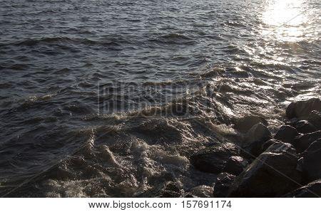 Lumpy sea and rocks on sunset. Lumpy sea at cloudy day