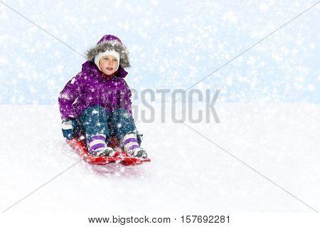 Little girl sliding in the snow. Christmas background.