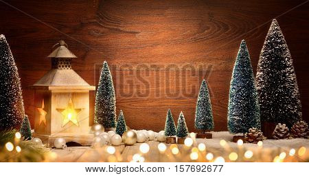 Christmas scene with a lantern trees baubles and blurred lights in front of an illuminated elegant dark wooden board as copy space