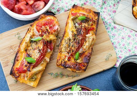 Grilled open faced sandwich tartine with tomato olives cheese and chicken