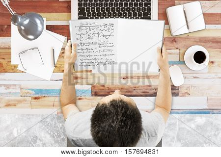 Top view of young businessman at office desktop holding open book with mathematical formuls. Education concept 3D Rendering