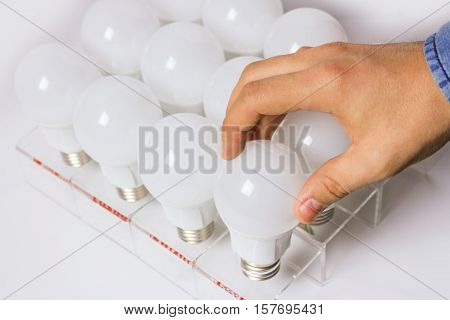 many led lamps. man's hand unscrews the light bulb.