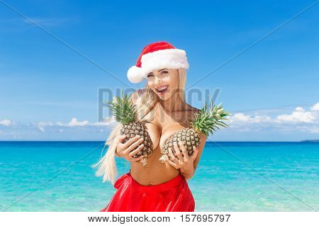 Beautiful cheerful blonde in Christmas hat and skirt holding a pineapple at the breast on the beach . Tropical sea in the background. New year holidays in the tropics.