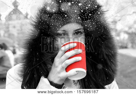 Yound Girl Drinks A Red Cup Of Hot Tea Black And White Filtered With Shiny Snowfall