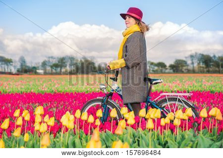 Smiling woman in a coat and hat on standing with her bike in a yellow and red tulips field