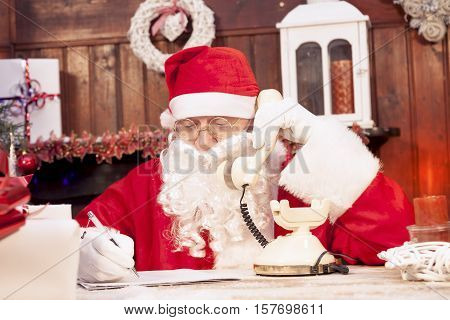 Santa Claus On The Phone At His Home Compiles The Wishlist For Christmas