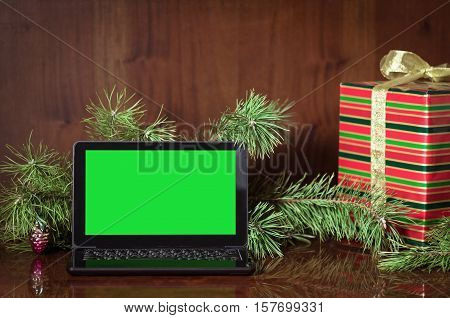 Christmas composition from a netbook a gift and pine branches. Green screen on the monitor for your projects.