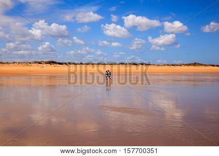 SANTANDER SPAIN - AUGUST 20: Couple walking on the El Puntal beach in Somo on August 20 2016