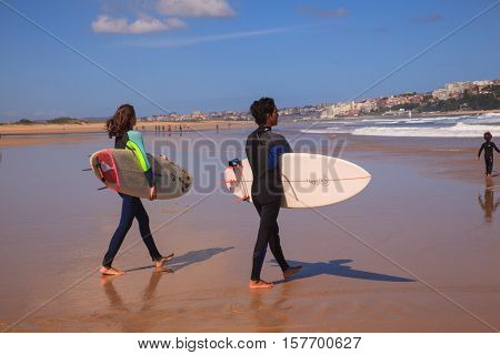 SANTANDER SPAIN - AUGUST 20: Surfer couple carrying their surfboard on the beach on August 20 2016