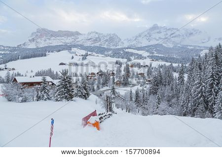 Majestic winter landscape and ski resort with typical alpine wooden houses in Italian Alps, Alta Badia, Italy, Europe