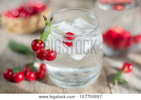 Cold water with ice and cherries. Morning light, the surface of unplaned planks and side. Selective focus.
