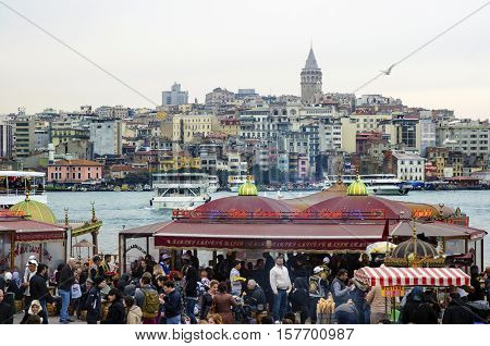 Istanbul Turkey - March 29 2013: Eating Grilled Fish Sandwich in Eminonu. Backplane the Galata Tower looks. The first thing that comes to mind when thinking of Istanbul is Eminonu-Karakoy and the places selling grilled fish sandwiches on the bank of Golde