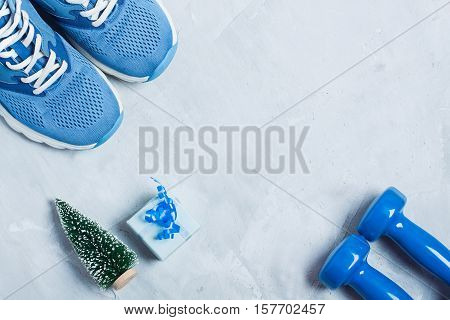Christmas Sport Composition With Shoes, Dumbbells And Blue Gift Box