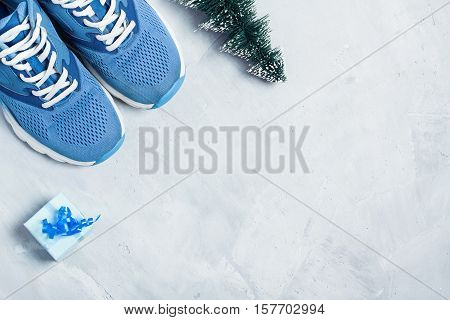 Christmas sport flat lay composition with shoes christmas tree and blue gift box on gray concrete background. Concept сhristmas special for healthy lifestyle and sport.
