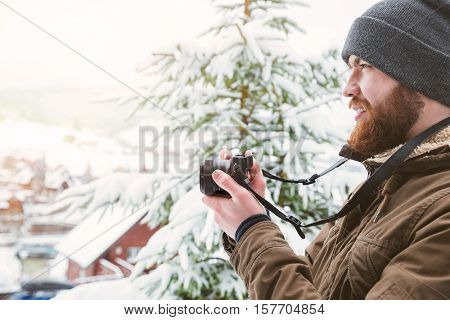Profile of focused young man using camera and taking photos in winter