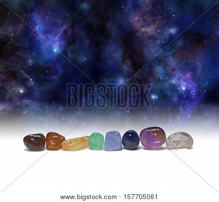 Cosmic Chakra Healing Stones - a row of chakra colored tumbled healing crystals set against a background of the Universe providing copy space above