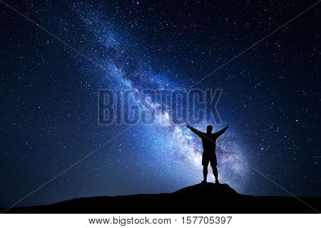 Milky Way with silhouette of a standing happy man with raised up arms on the mountain. Night landscape with beautiful galaxy. Universe. Night sky with stars and colorful Milky Way. Bright stars