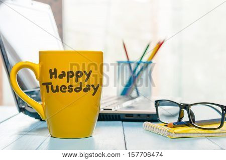 Happy tuesday word on yellow morning coffee cup at blurred home or office background.