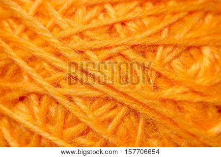 Woolen yarn ball, skein of tangled orange sewing threads, selective focus
