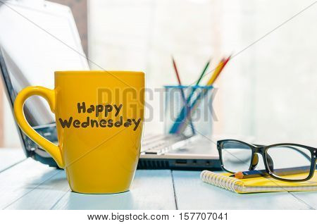 Happy Wednesday word on yellow morning coffee cup at blurred home or office background.