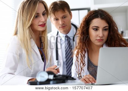 Group Of Doctors Using Laptop Pc Sitting In Office
