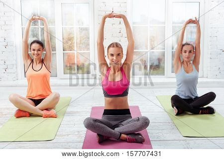 Exercises time. Three young pretty girls having their yoga classes together while doing Asanas and feeling happy.