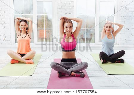 Care about health. Three pretty young girls doing yoga exercises while spending time in a gym and enjoying asanas.
