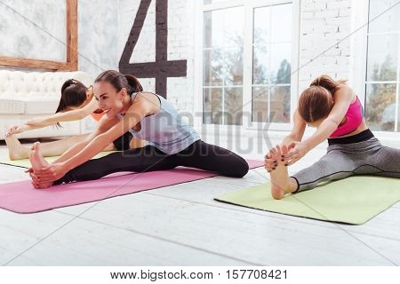 Sport brings harmony. Three joyful young girls training and spending time in a fitness studio while stretching.
