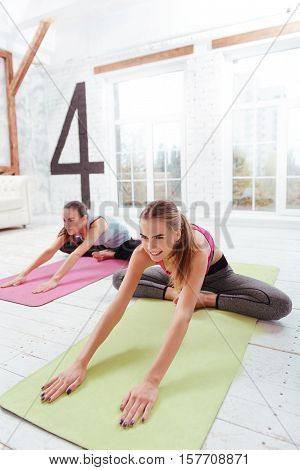 Through the pain. Two concentrated young girls doing stretching and exercising while spending day in a gym,