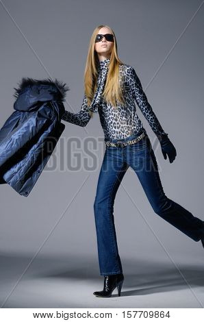 Full body Studio shot of a model in jacket and sunglasses on gray background