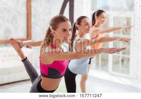 You know you can. Three graceful young women having group stretching classes and doing exercises while spending day in a gym.