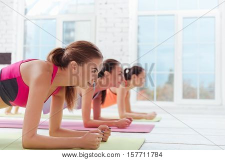 One more minute. Three active young women standing in plank while training and spending time in fitness studio together.