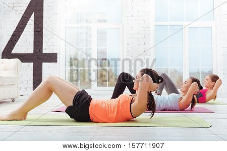 One more time. Three joyful young women doing pushups and training hard while enjoying day in gym.