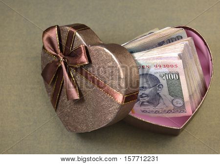 Hundred Indian rupee currency notes in a heart shaped gift box. Concept for 'Cash rewards' or perks.