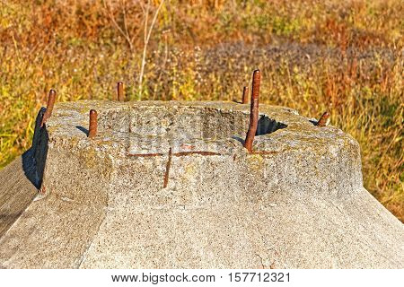 Detail ob big concrete abandoned construction with vertical metal rods on the background of dried grass in autumn